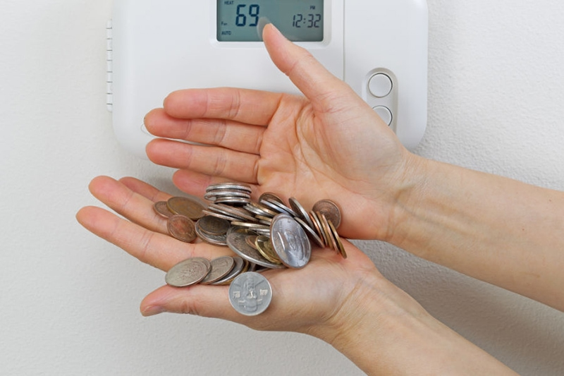 Coins in hand by thermostat