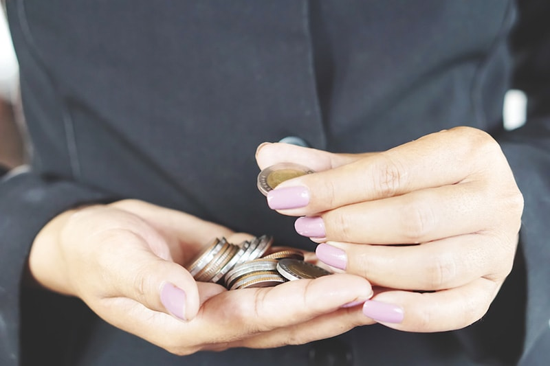 A woman counting coins in her hands | Afford New HVAC Financing | How Can I Afford a New AC System (and Other HVAC Equipment)?