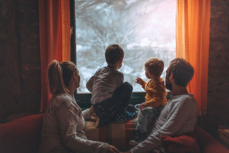 family looking out window in winter